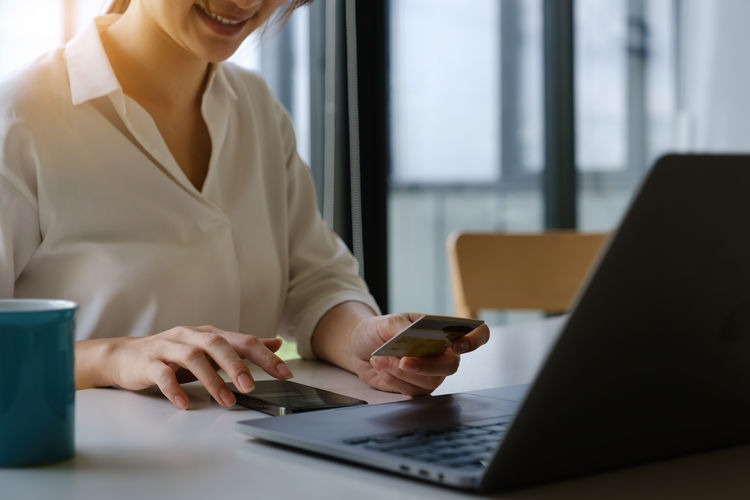 Woman holding credit card over laptop