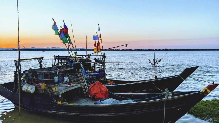 Fishing boats moored in sea at sunset