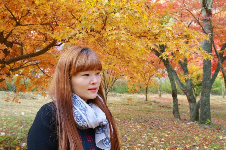 Beautiful young woman standing at park during autumn