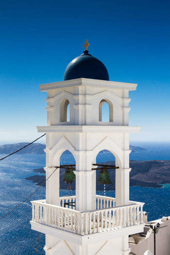 Bell tower against sea and blue sky