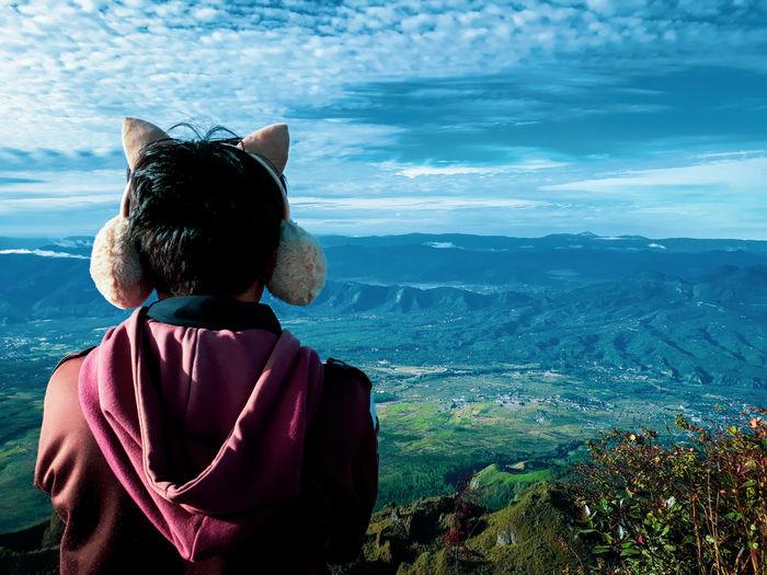 Rear view of man wearing ear puff against landscape