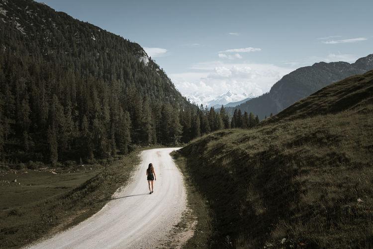 Woman walking on dirt road against sky