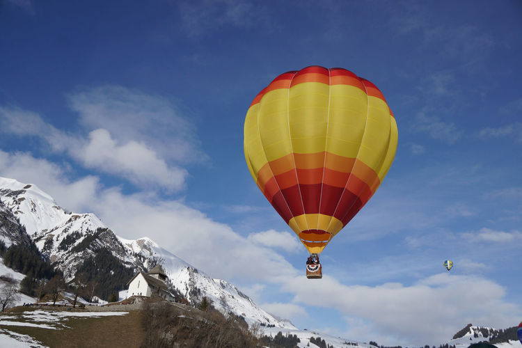 Hot air balloons flying over snowcapped mountains against sky