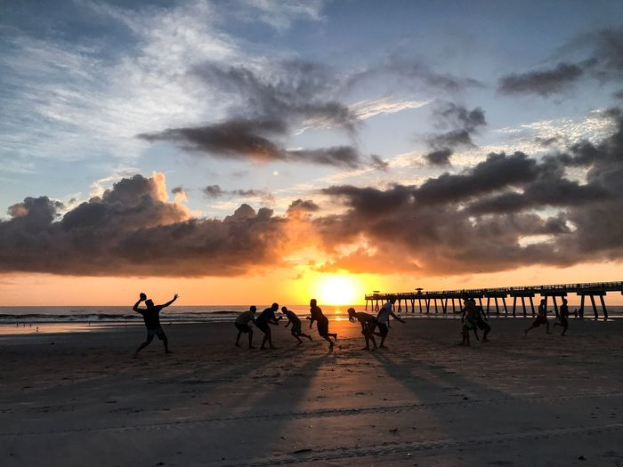 People playing on sand against sea during sunset