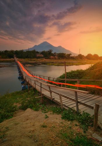 Sunset bridge Mountain Sunset Tree Water Lake Sky Landscape Mountain Range Mountain Peak Idyllic Coast Dramatic Sky Tranquil Scene Commercial Fishing Net Horizon Over Water Zermatt Snowcapped Mountain Scenics Non-urban Scene Majestic Atmospheric Mood Sky Only Storm Cloud Rocky Mountains Remote Fence