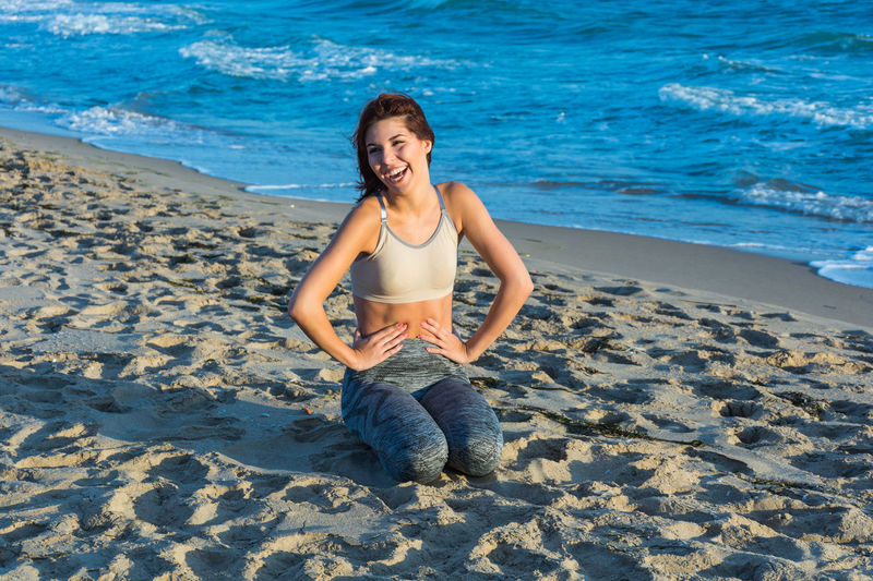 Beach Beautiful Woman Emotion Front View Full Length Happiness Land Leisure Activity Lifestyles Looking At Camera One Person Portrait Real People Sand Sea Smiling Water Women Young Adult