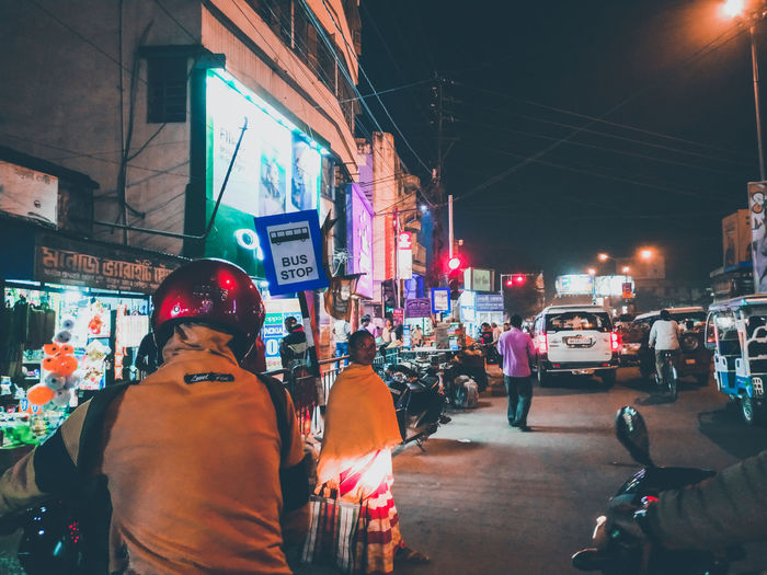Rear view of people on city street at night