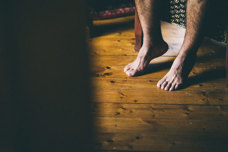 Low section of man relaxing on hardwood floor