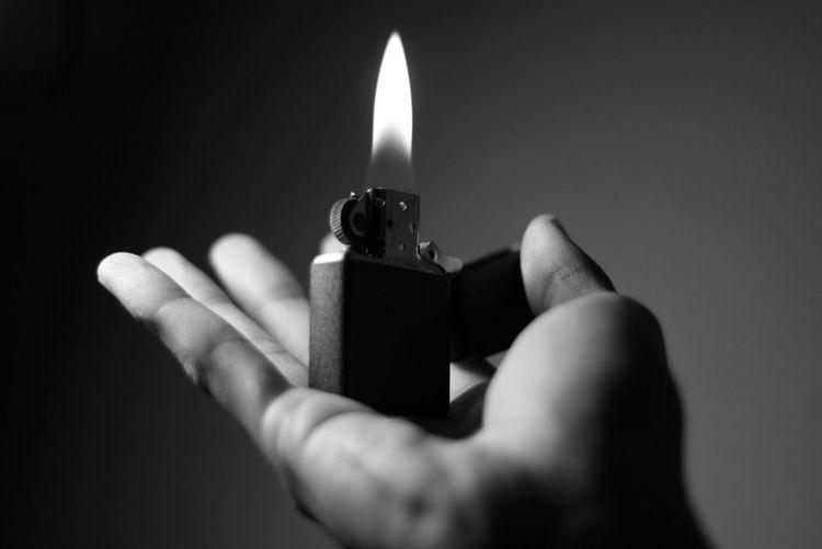 Cropped hand holding cigarette lighter
