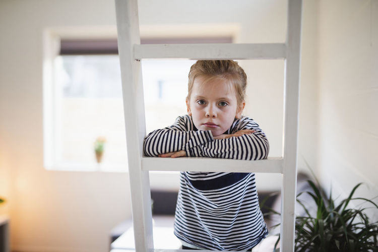 Portrait of boy standing by window at home