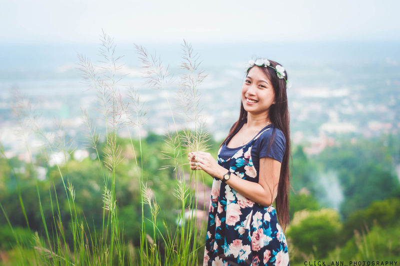 Portrait of happy woman holding plants while standing against landscape