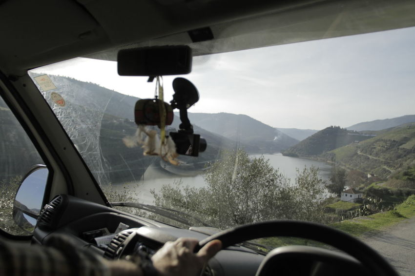 Looking through windscreen at mountain path and river Car Car Interior Close-up Dashboard Day Human Hand Land Vehicle Landscape Mode Of Transport Motion Mountain One Person Outdoors People Real People Road Sky Steering Wheel Transportation Vehicle Interior Windscreen Windshield