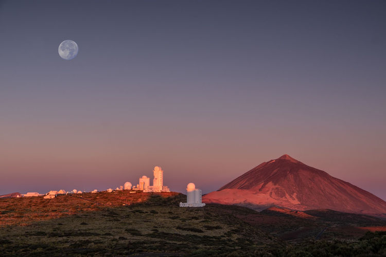 Observatory in teide nationalpark with volkano inthe back at sunrise with moon above.