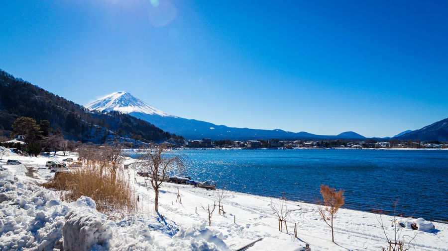 Scenic View Of Lake Kawaguchi And Mt Fuji Against Blue Sky During Winter