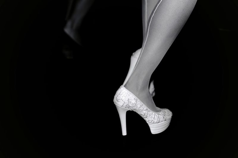 Low section of women wearing high heels at night