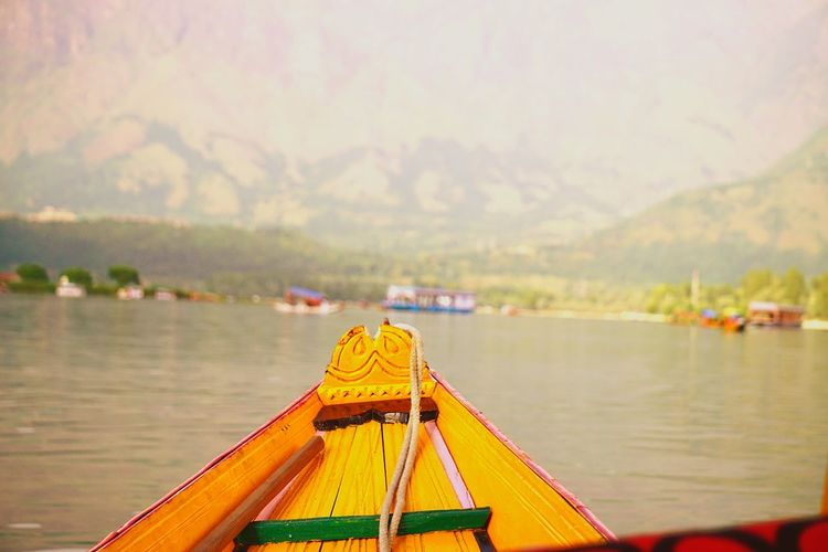 Cropped image of boat on lake against mountain