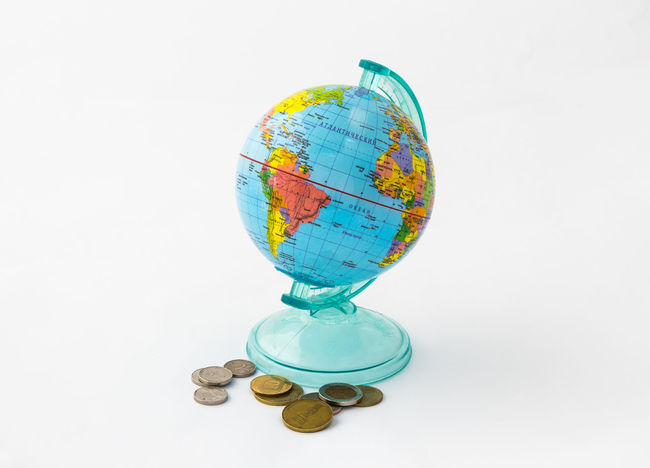 A money box made in the form of a globe, the planet Earth with a money slot at the top stands near to several coins, isolated on a white background. Business Currency Earning Earth Isolated Art Bank Banknote Buy Cash Coin Coins Design Exchange Finance Globe Israel Money Pay Planet Shekel Stock Studio Shot Wealth White Background