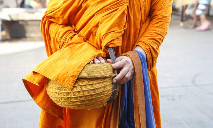Midsection of monk with container standing in temple