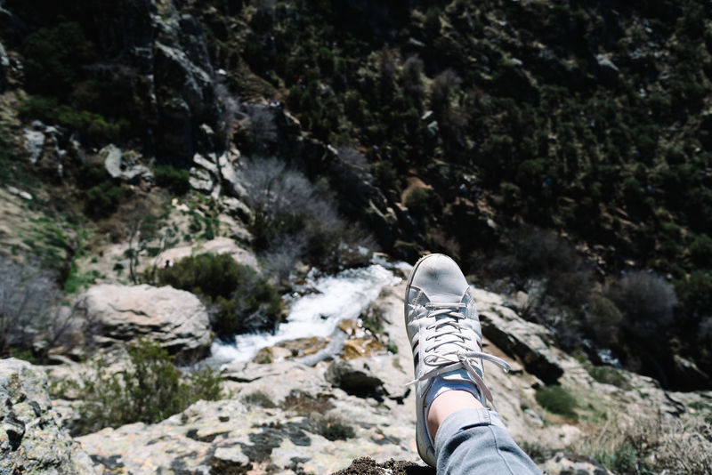 Sneaker against waterfall Adventure Day Hiking Human Body Part Human Leg Leisure Activity Lifestyles Low Section Men Mountain Mountain Range Nature One Person Outdoors People Personal Perspective Real People Rock Rock - Object Shoe Sneakers Stream - Flowing Water Tree Waterfall Waterfalls