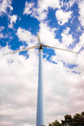 Low angle view of wind turbine against cloudy sky