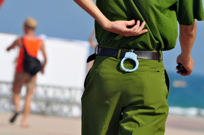 Close-up of police with handcuff walking at beach