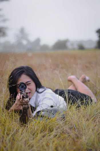 Young woman aiming while lying on grassy land against sky