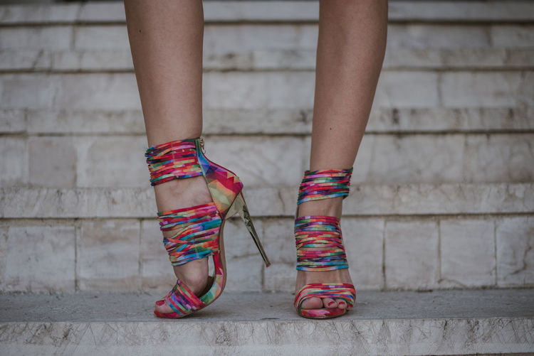 Low section of woman wearing multi colored stiletto standing on staircase