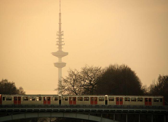 Train On Railway Bridge Against Heinrich-Hertz-Turm During Foggy Sunrise