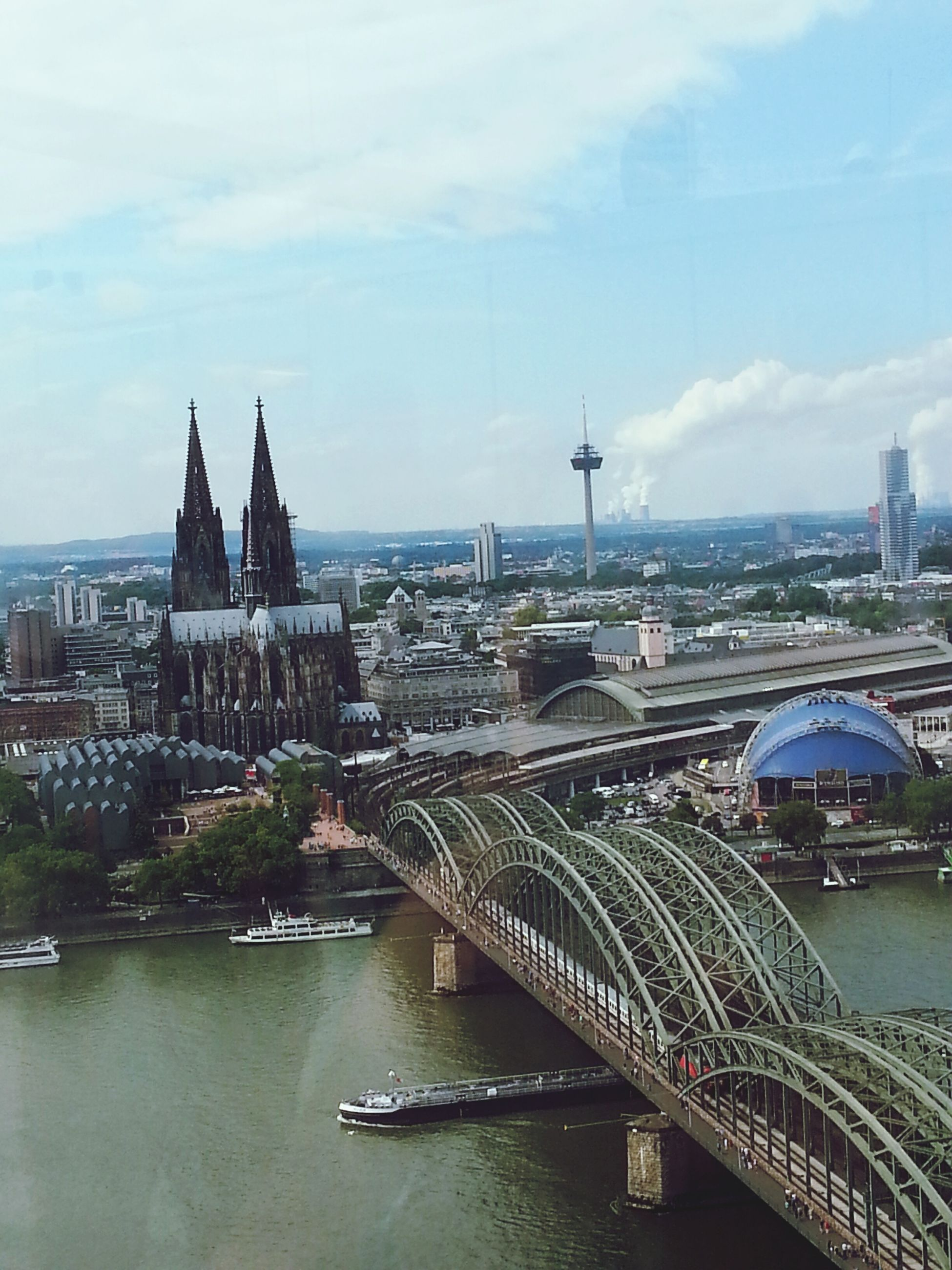 architecture, built structure, building exterior, water, city, sky, river, transportation, cityscape, high angle view, cloud - sky, bridge - man made structure, connection, mode of transport, travel, travel destinations, day, outdoors, city life, canal