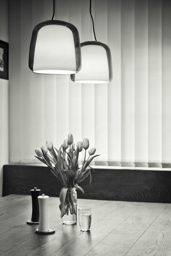 Flower vase on table against wall at home