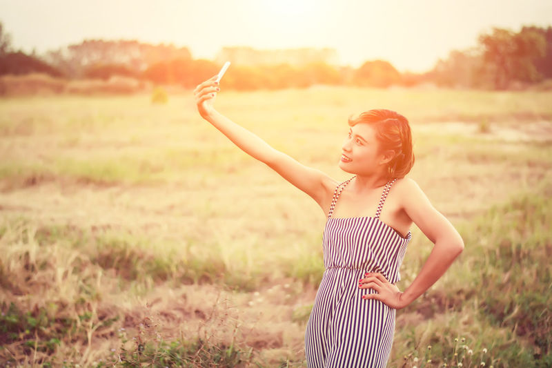 Woman taking selfie with smart phone on field