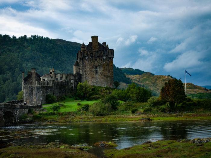Historic eilean donnann castle by lake against sky