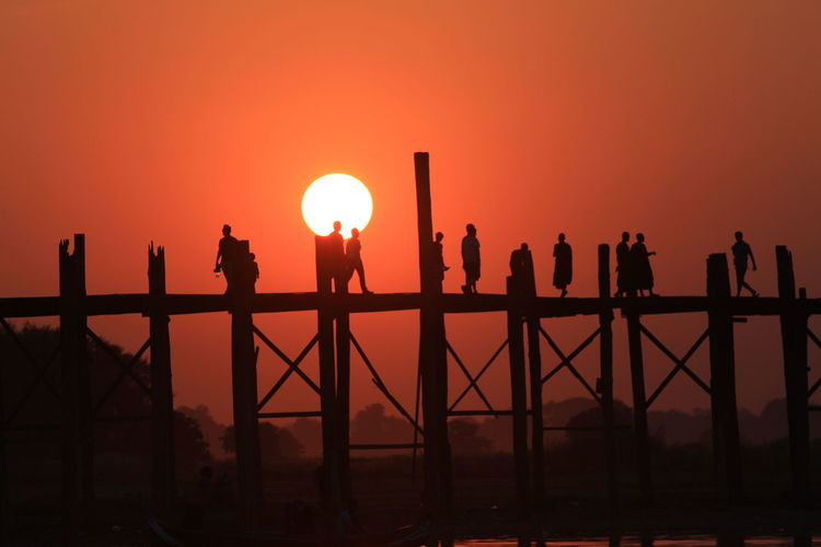 Silhouette people on u bein bridge over river during sunset