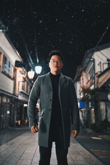 Portrait of young man standing on street at night