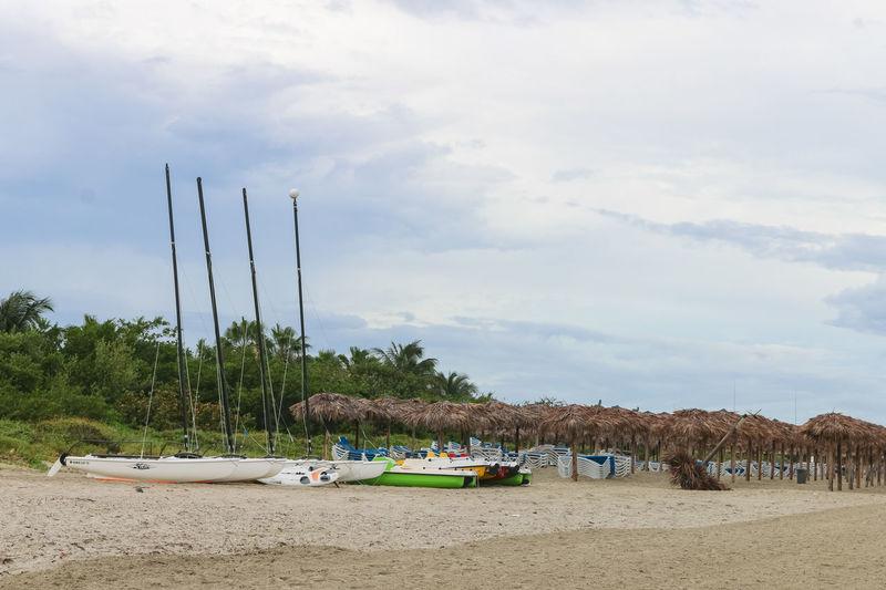 Sailing catamarans without sails on the beach, Cuba, Varadero Cuba Cuba. Varadero Parking Lot Varadero Beach Cloud - Sky Day No People Outdoors Resort Sailboat Sand Scenics Sky Sunshade Tranquil Scene Tree Umbrella