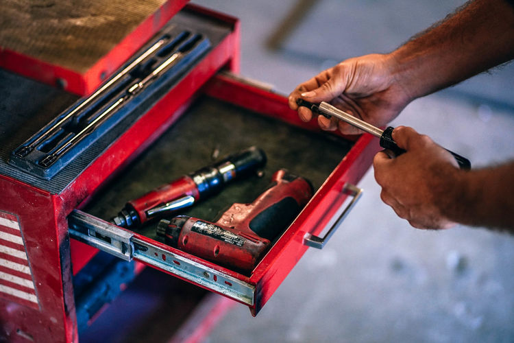 Toolbox in the workshop. Man holds a screwdriver. Fix  Man Mechanic Mechanical Red Service Closeup Collection Design Engineering Equipment Fixie Hand Hardware Holder Indoors  Instrument Male Metal Metallic Nozzle Pliers Product Repair Screwdriver