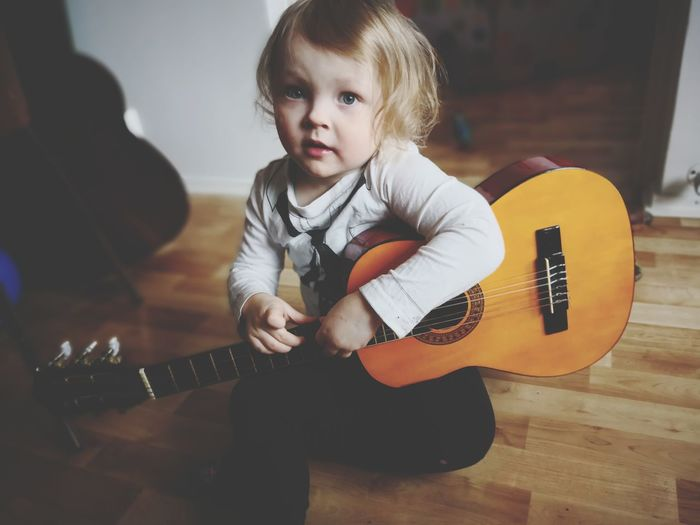 Portrait of cute girl playing guitar while sitting at home