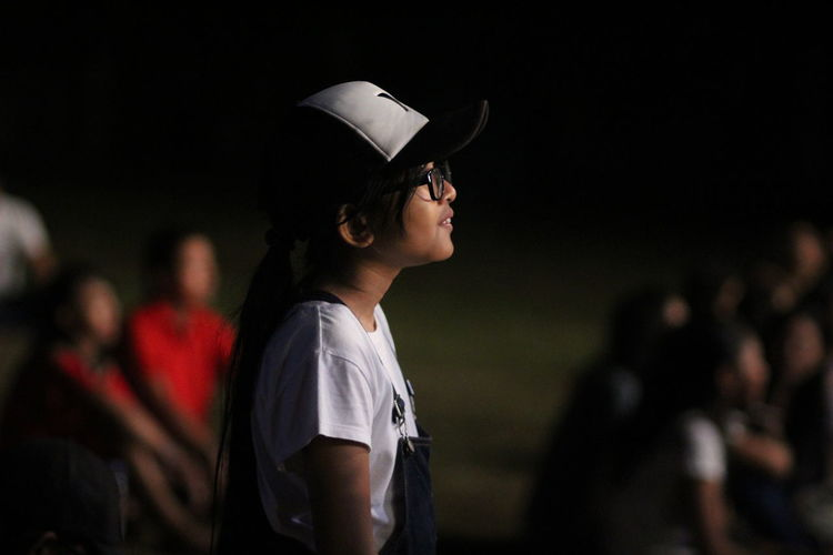 Side view of girl looking away on land at night