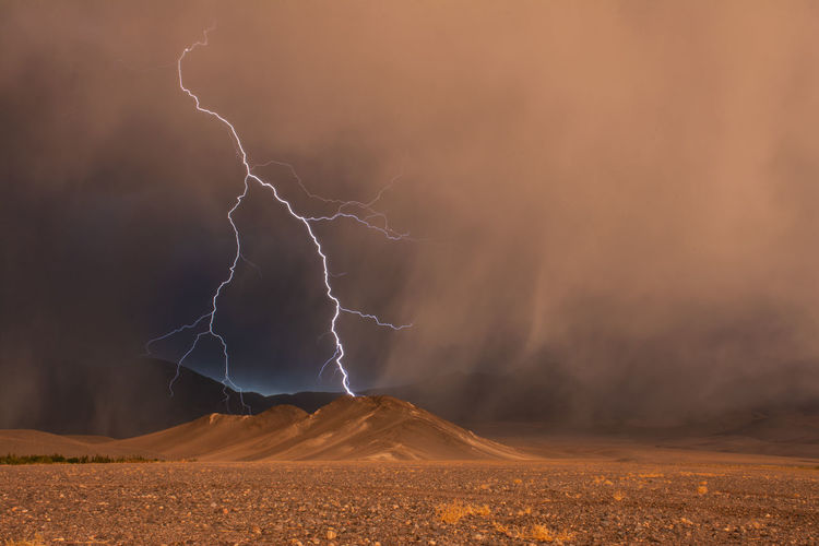 View of lightning over mountains during storm during sunset