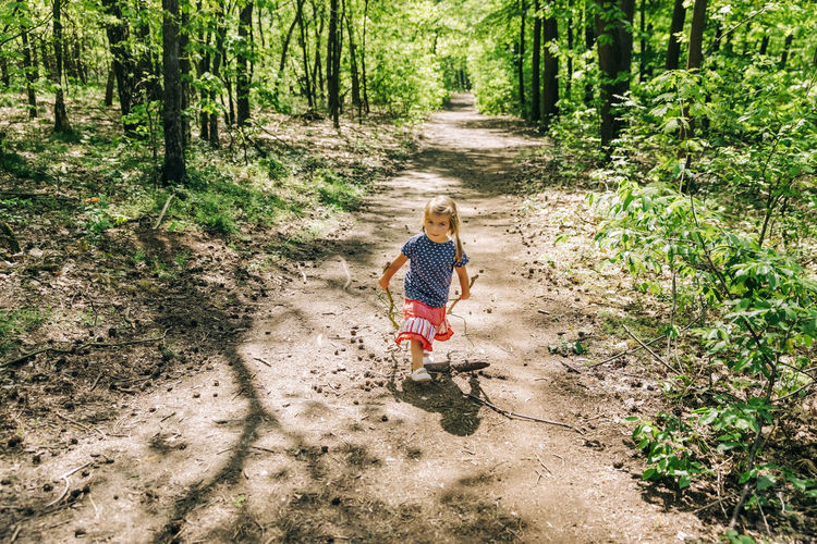 Cute girl walking on dirt road in forest
