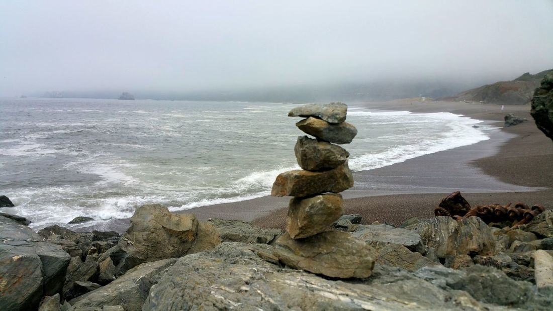 Balanced meditation stones in foreground offset a misty foogy ocean Zen Meditation Atmospheric Dramatic Moody Foggy Fog Sentinel Solitary Countryside Clouds Mysterious Misty Romantic Dreamy Water Sea Wave Beach Sand Pebble Sky Horizon Over Water Landscape Tide Surf Coast Stack Rock Seascape Coastline