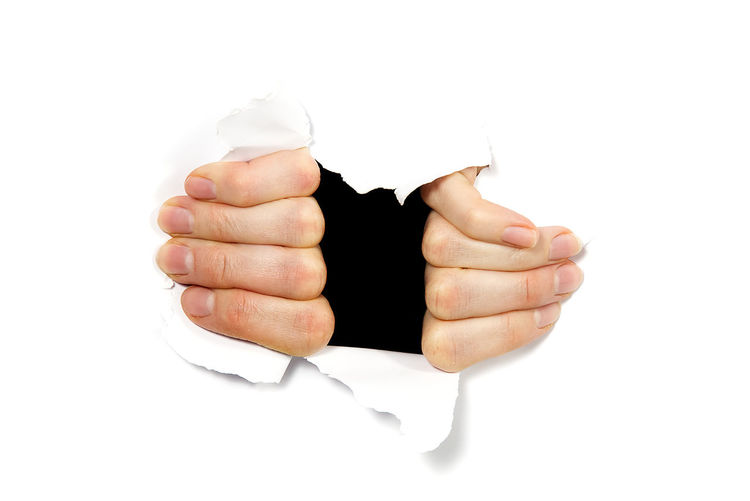 Cropped hands tearing paper