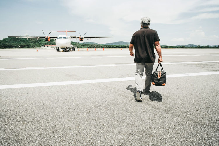 Rear View Of Man Carrying Bag While Walking On Airport Runway Against Sky During Sunny Day