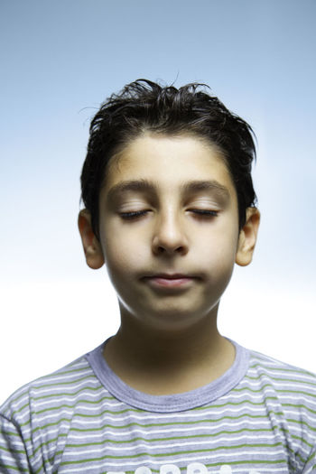 Close-up of boy meditating against clear sky