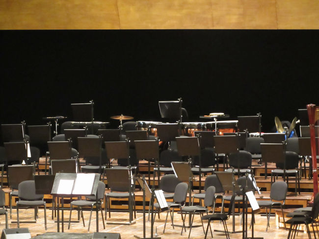 Empty chairs stand on stage in concert hall Acoustics Classic Music Opéra Staff Stage Symphony Theater Art Chairs Classical Concert Conservatory Culture Empty Entertainment Hall Harmony Instruments Interior Melody Musical Nobody Orchestra Stave