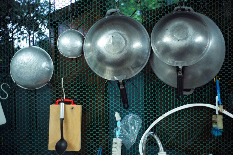 Close-Up Of Kitchen Utensils Hanging On Metal Grate