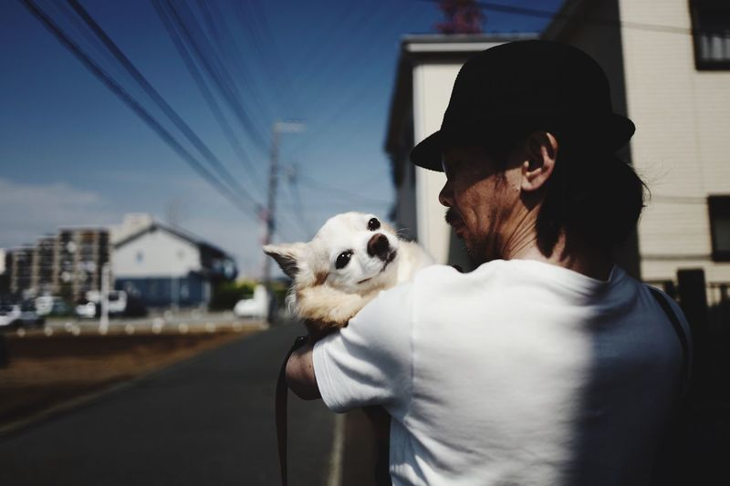 Man Carrying Dog By Street In City