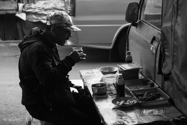 Man drinking tea while sitting on table