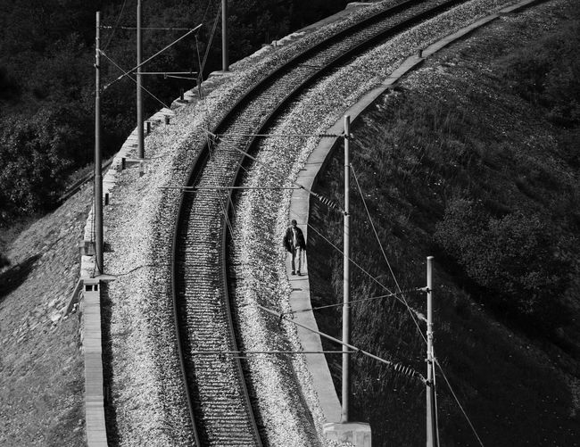 Man walking by the railway in Rijeka, Croatia Black And White Blackandwhite Canon Connection Detail Engineering Outdoors Photography Power Supply Rail Railroad Railway The Way Forward Track Tranquility Vanishing Point