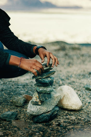 Low section of man stacking stones